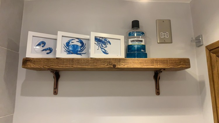 bracket shelves with cast iron brackets and solid wood shelf in bathroom
