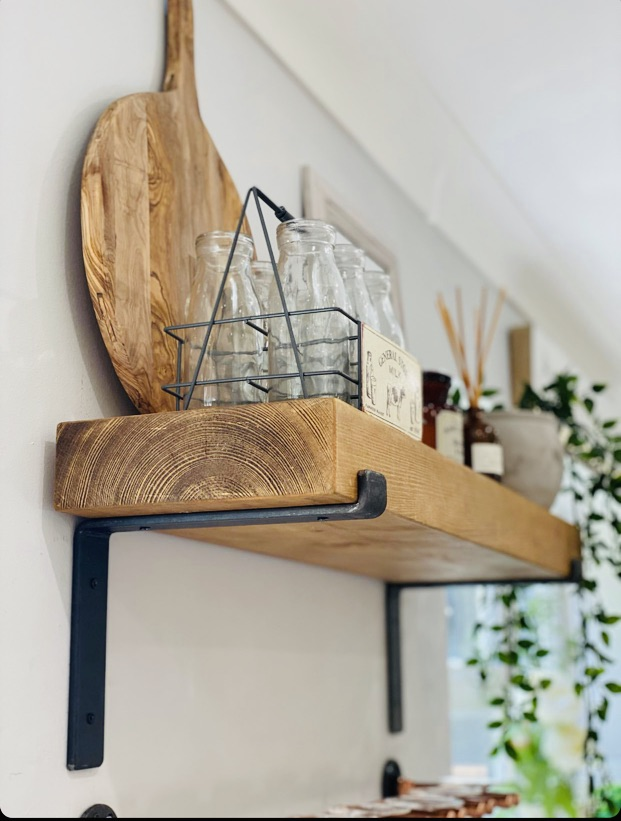 solid wood shelf with cast iron scaffold style brackets in kitchen.