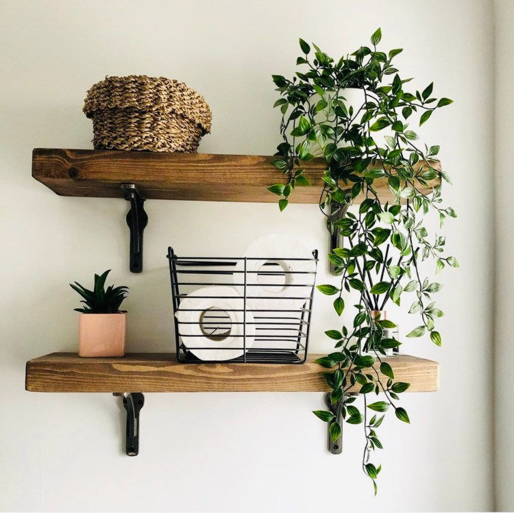 solid wood bathroom shelves with cast iron metal brackets, styled with houseplant on white wall.