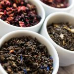 A variety of loose-leaf teas in small bowls.