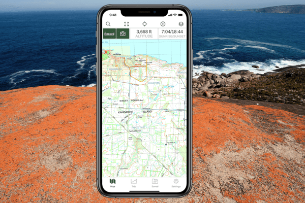 iphone with South Australia topo map of Kangaroo Island in foreground with image of coast in background.
