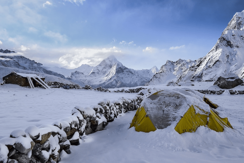 Jagged, snowy mountain peaks with tent in foreground