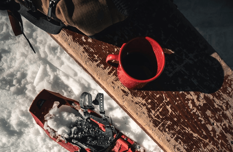 coffee cup, backpack, snowshoe and bench on snow