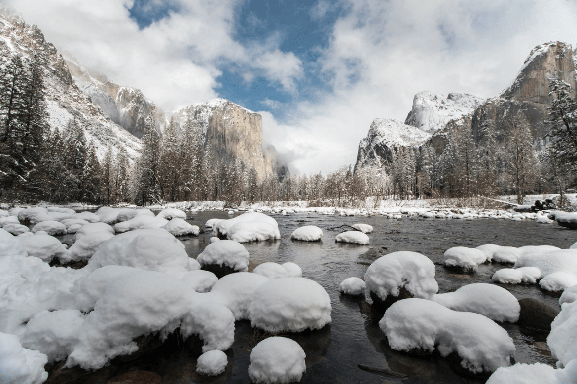 Snowy river rocks backdropped by snow covered El Capitan, Yosemite Valley's most prominent monolith.