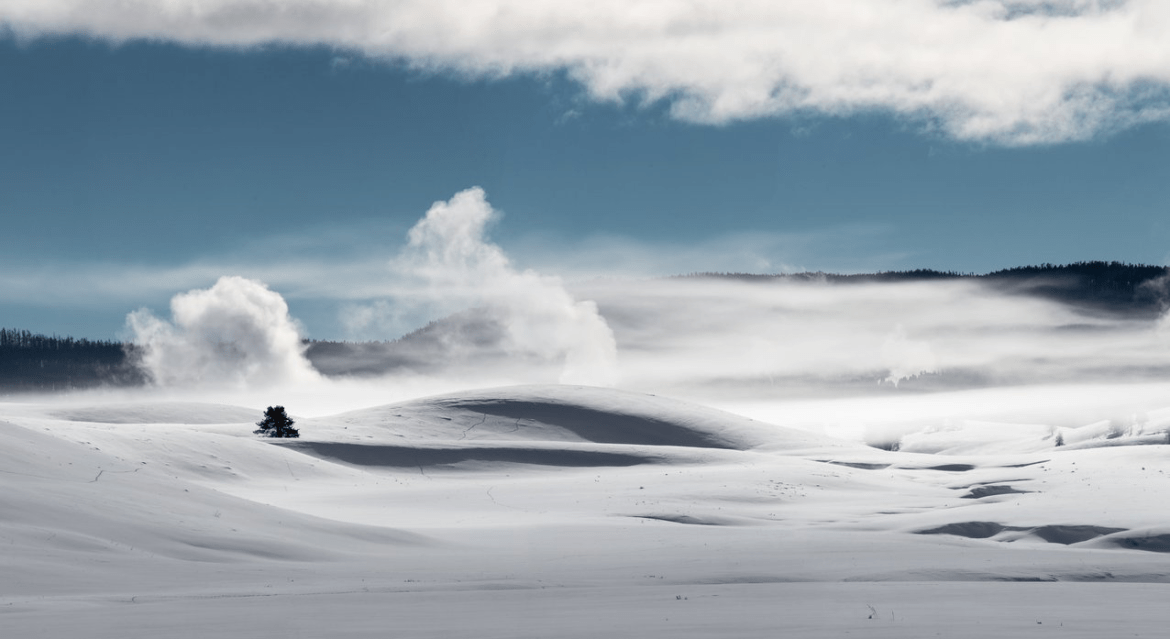 Wide open snow field with steam rising from geothermal pools, under a blue sky.
