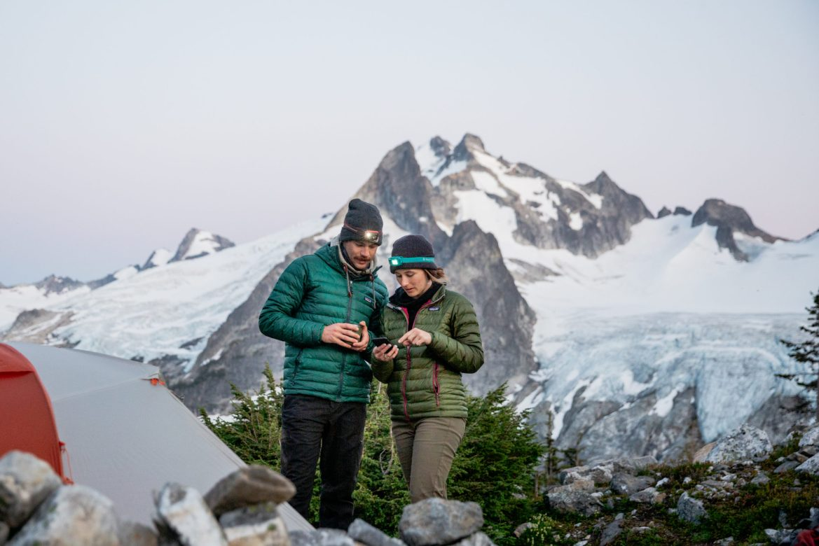 A man and a woman looking at a phone screen. There is a tent in the foreground and a large mountain in the backdrop.