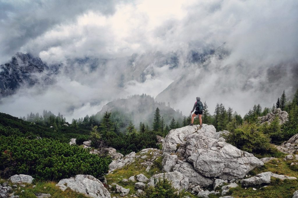 A woman hiker standing on a rock looking out into a foggy mountain valley.