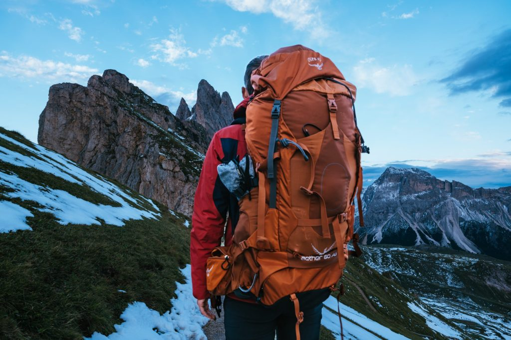 A man with an Osprey backpack facing away from the camera and looking at a mountain
