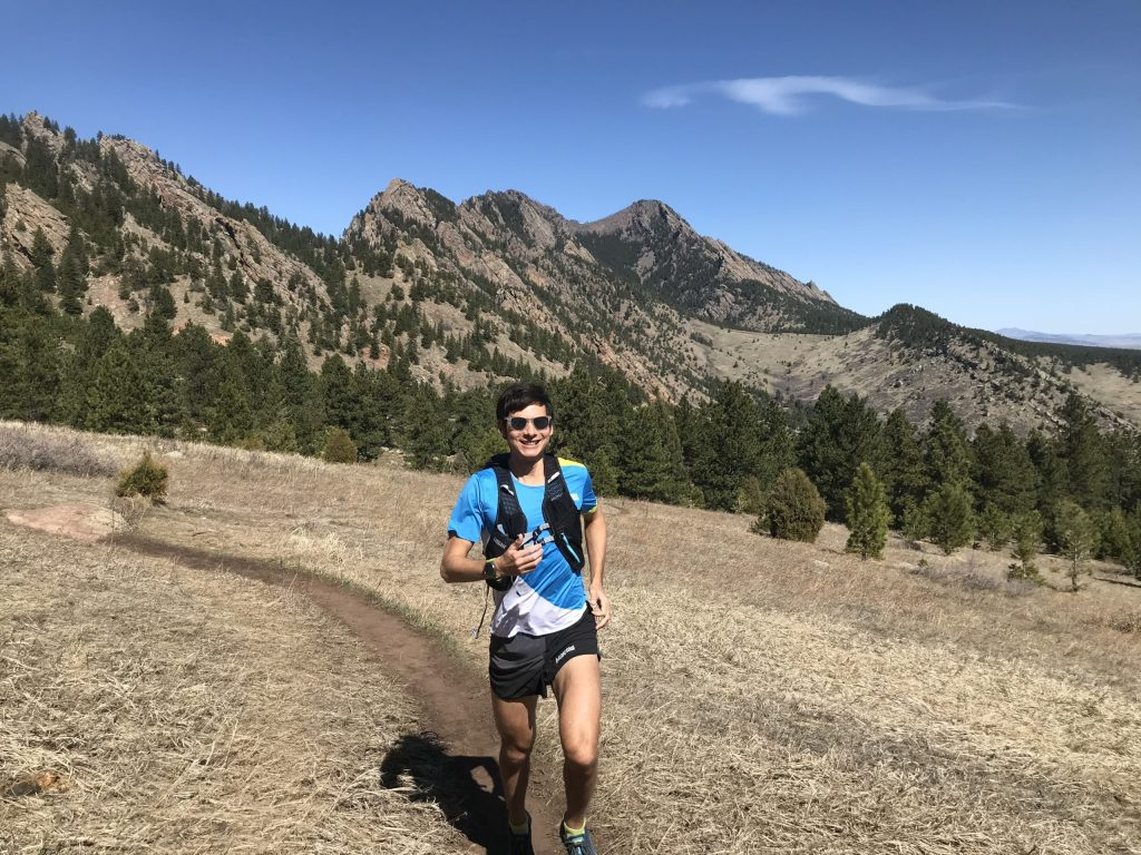Ultra runner Sage Canaday running on a trail with mountains in the background.