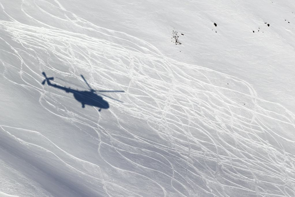 A shadow of a helicopter on a snow field with ski tracks