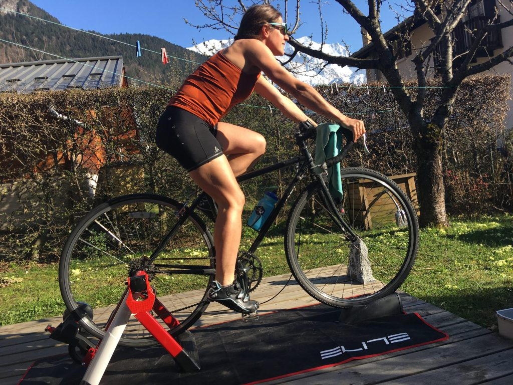 Mountain athlete Hillary Gerardi riding a stationary bike in her backyard in France.