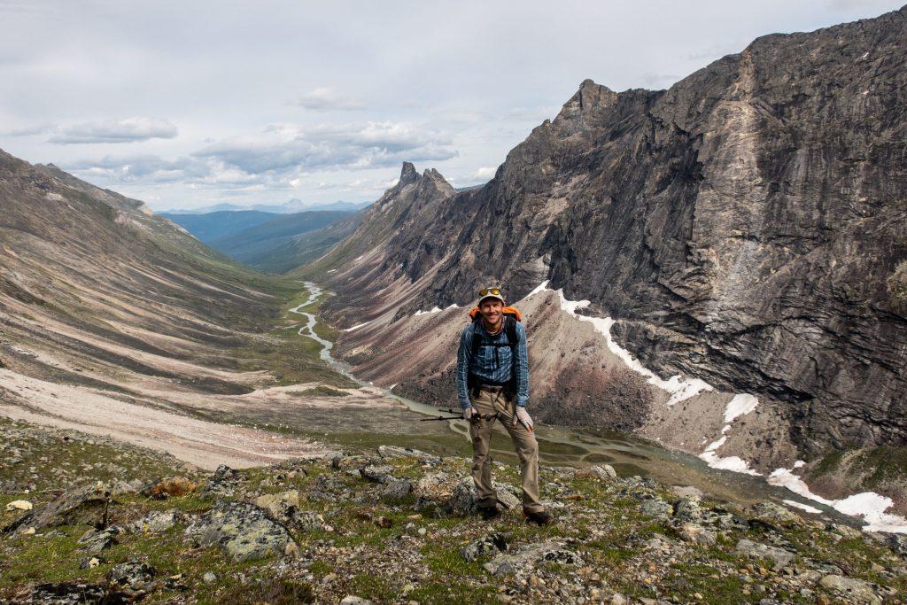 Backpacker Andrew Skurka standing on a ridge above a wide valley in Alaska's Brooks Range.