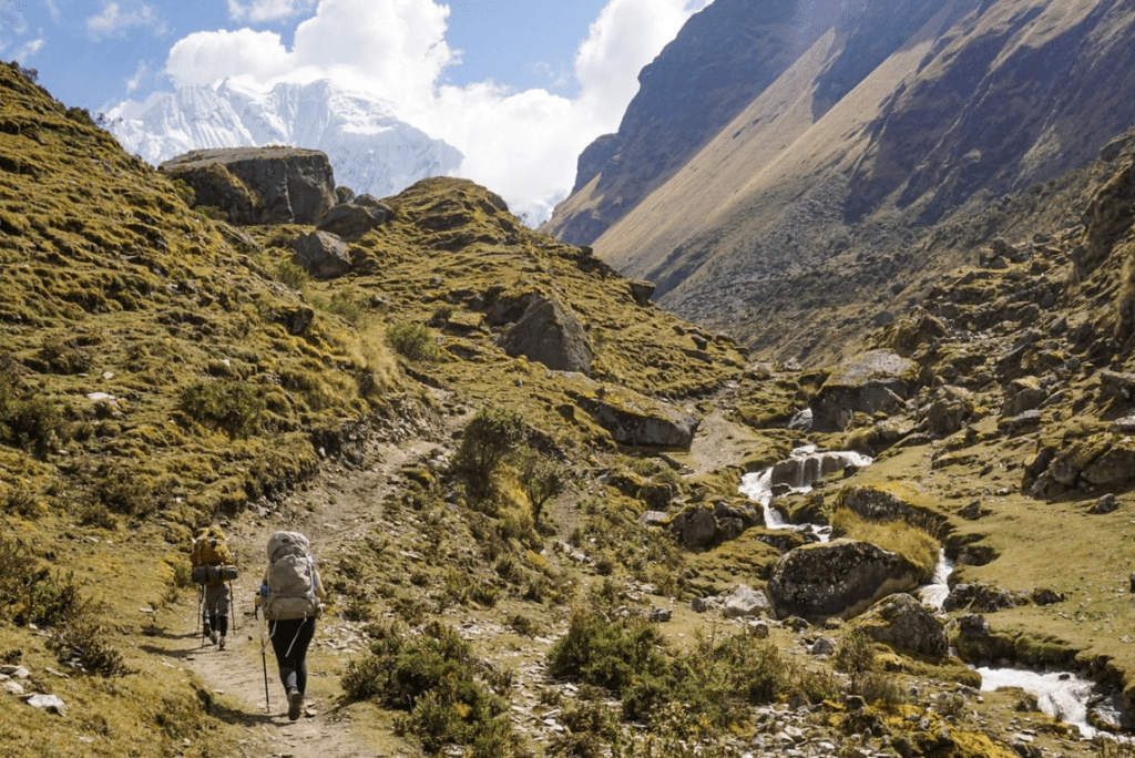 two backpackers climbing a hill on a rugged trail in Peru