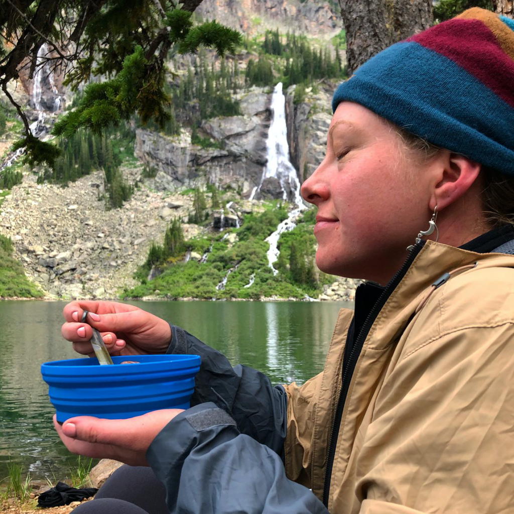 a woman enjoys a bowl of food in front of a waterfall