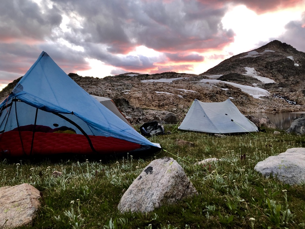 A solo tent and a two-person tent sit on a mountainside under a pink and gold, cloudy sunset.