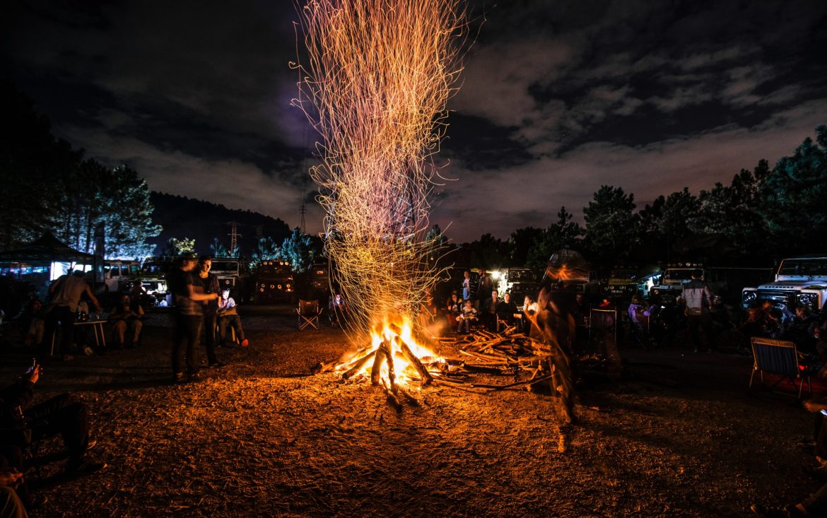 People stand around a bonfire at night with a flock of jeeps parked in the background.
