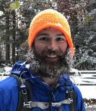 the host of the podcast Andrew Baldwin wearing an orange hat and blue jacket with a frosty beard, smiling