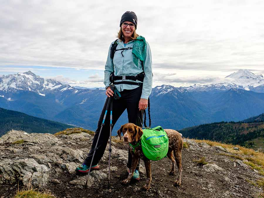 Aaron poses for the camera with her dog, who's loaded down with a dog backpack. Aaron holds her hiking poles and wears a backpack. They are standing in the alpine, with snowcapped-mountains behind.