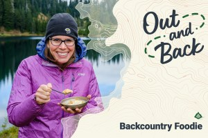 Backcountry Foodie smiles while eating a bowl of food in the backcountry.