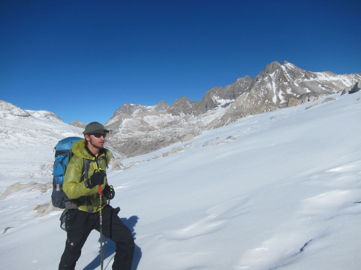Justin Lichter backcountry skis across a wind-swept snowfield. Barren, rocky peaks jut out of the snow behind him.