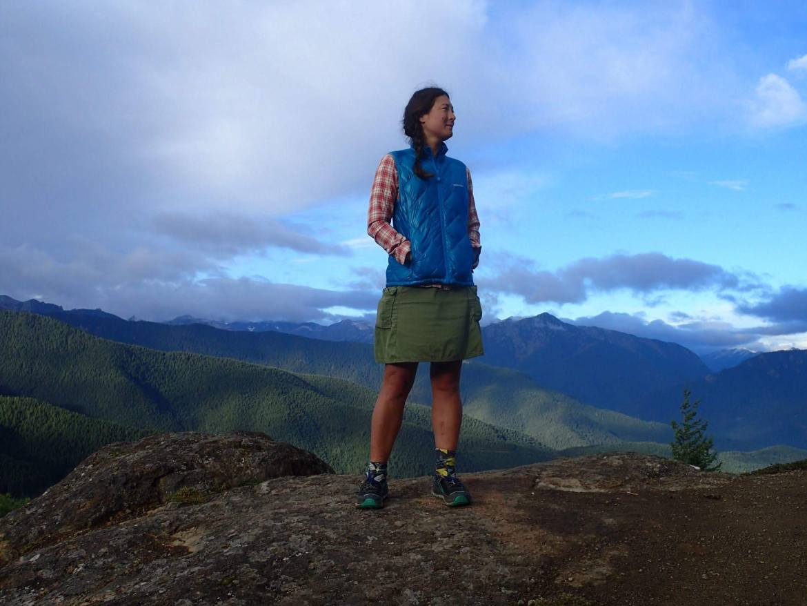 Snorkel stands on a mountain top, looking off her shoulder into the distance.  Green and blue mountains extend behind her.