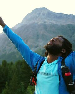 Will Robinson raises his arms above his head. His eyes look up to the sky. A mountain looms behind him.