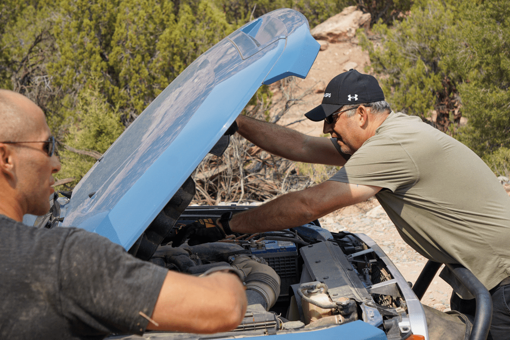 A man fixing a vehicle with the hood up.