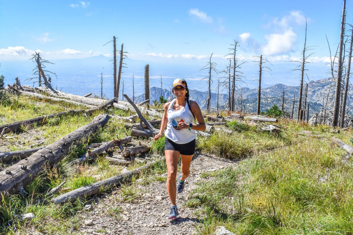 A runner passes by a burned forest with mountains in the background. The sun is shining and she's smiling.