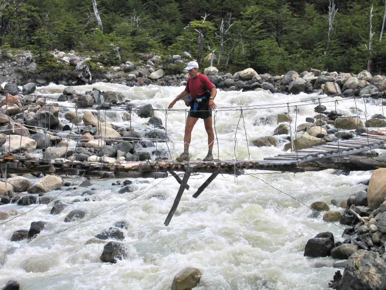Buzz walks across a log suspension bridge over a raging river.