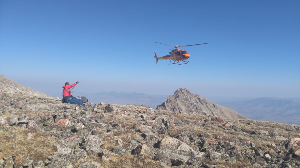 A search and rescue person sits on a rocky alpine field. A helicopter circles overhead.