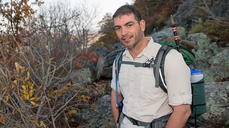 Sean Gobin smiles while standing on a rocky trail. He's wearing a backpack and button-down shorts sleeve shirt.