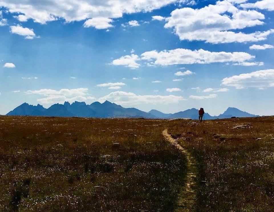 A backpacker stands on the horizon, in front of a single track trail through a meadow. Peaks loom in the distance.
