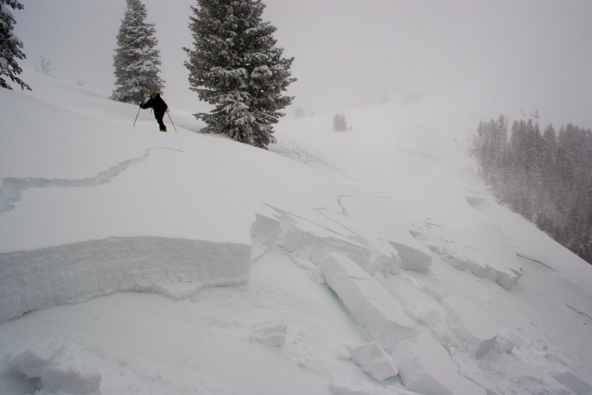 A skier crosses over the remnants of an avalanche slide.
