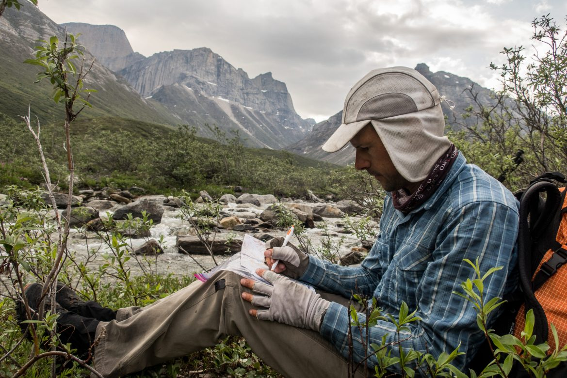 Skurka sits with his back against a backpack while taking notes. A river flows behind him, and peaks loom in the distance.