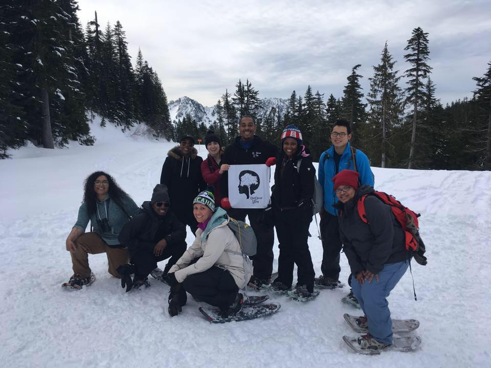A group of snowshoers smile for the camera on a snow-covered trail. Someone in the middle is holding a sign with the Outdoor Afro logo.