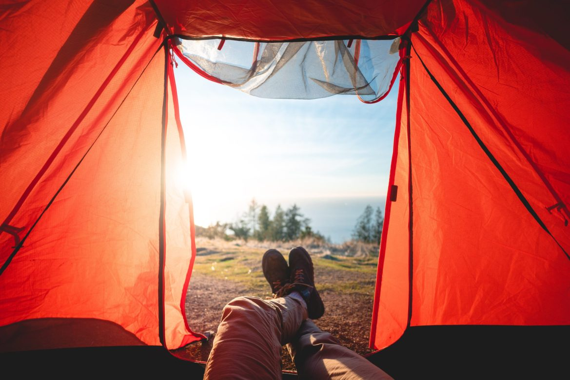 Feet poke out of a tent. Pine trees and the ocean are visible in the distance.