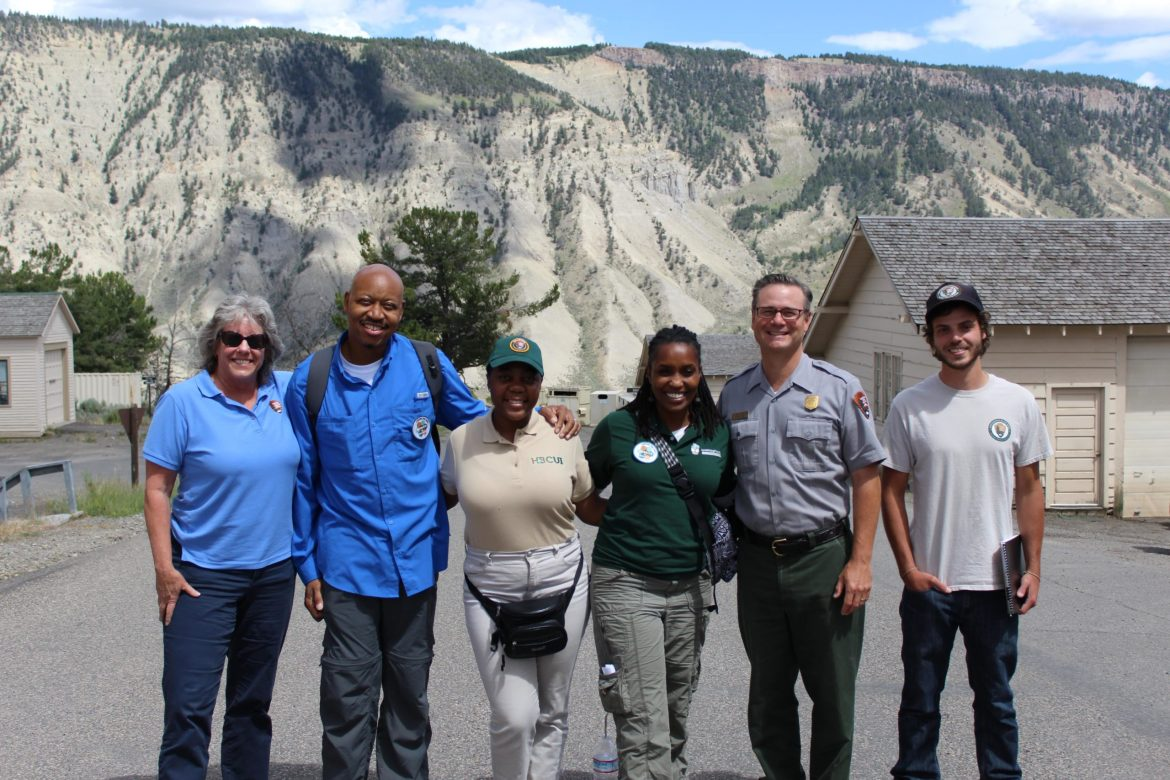 Angelou poses for the camera with five other NPS people. They are smiling and standing in a line in front of big rock walls in the background.