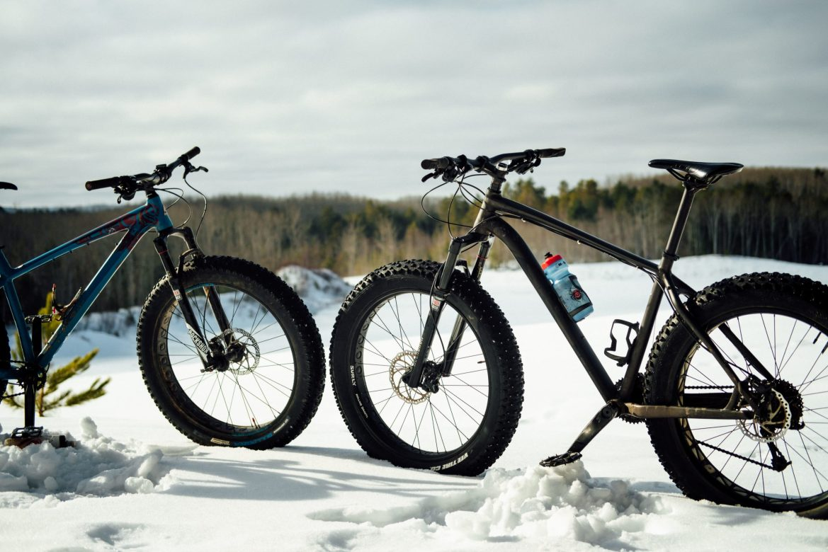 Two fat tire bikes face each other in the snow.