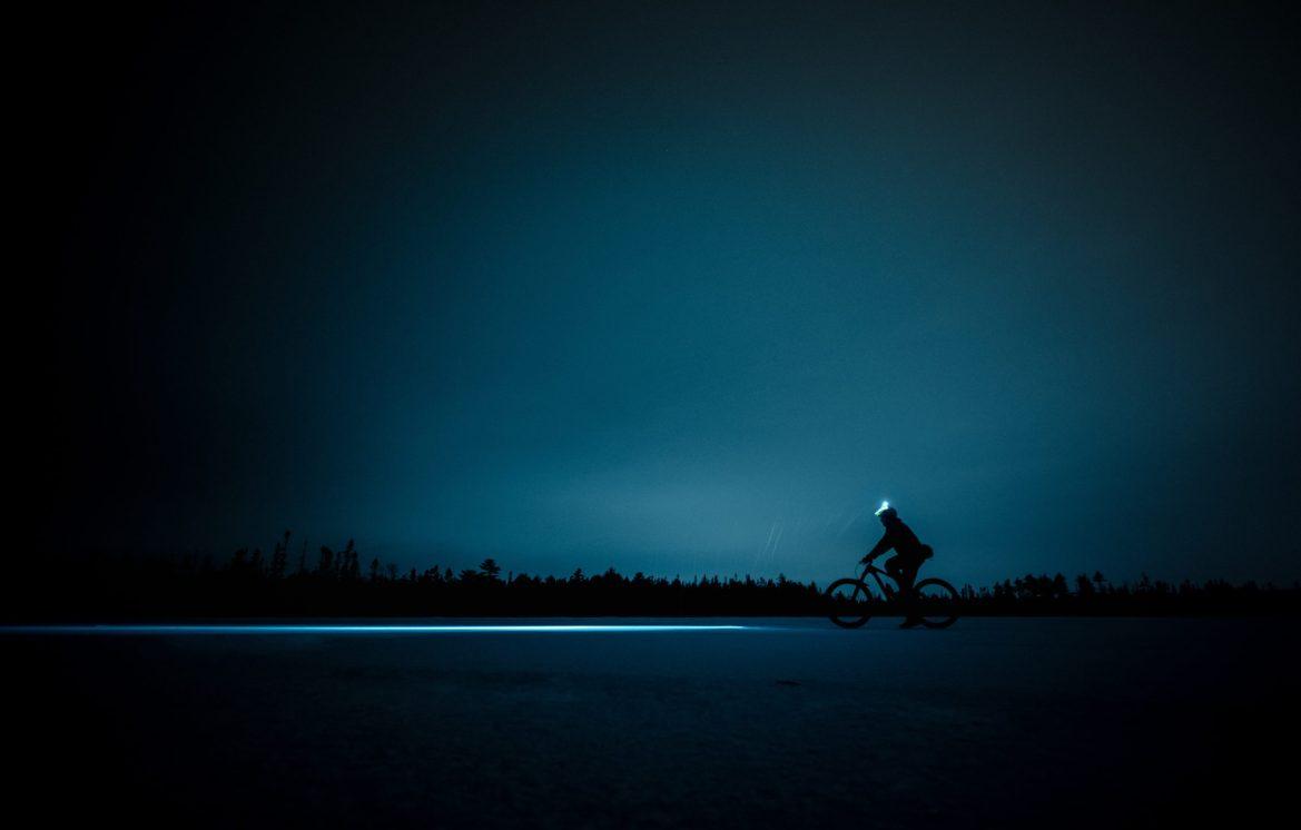 A fat biker rides over a snowy plain in the dark.
