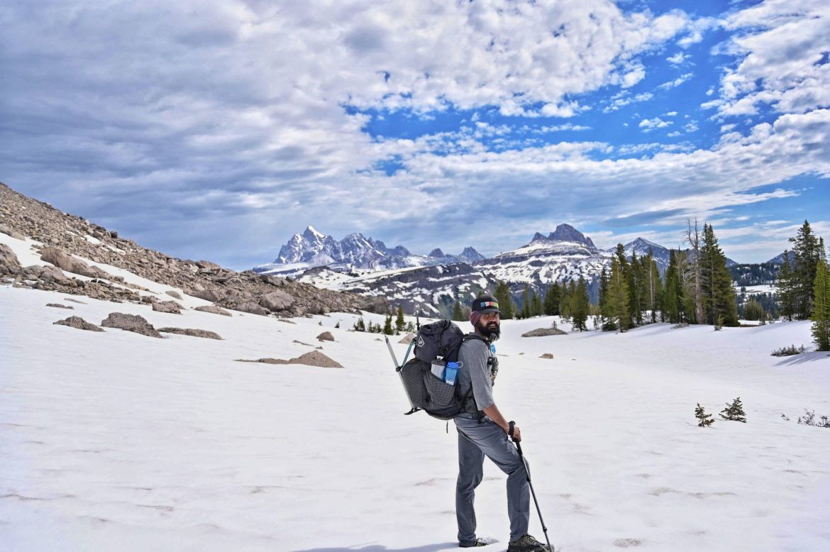 Anu stands in a snowfield with jagged peaks in the background. He's holding hiking poles and carrying a big backpack.