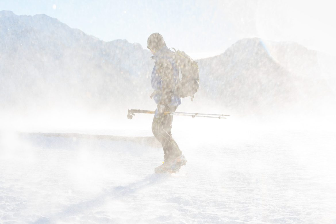 A hiker turns their face against the wind. They're carrying poles, wearing crampons, and have a backpack, hood, sunglasses, and winter coat. They're standing on a snowfield with mountains in the background.