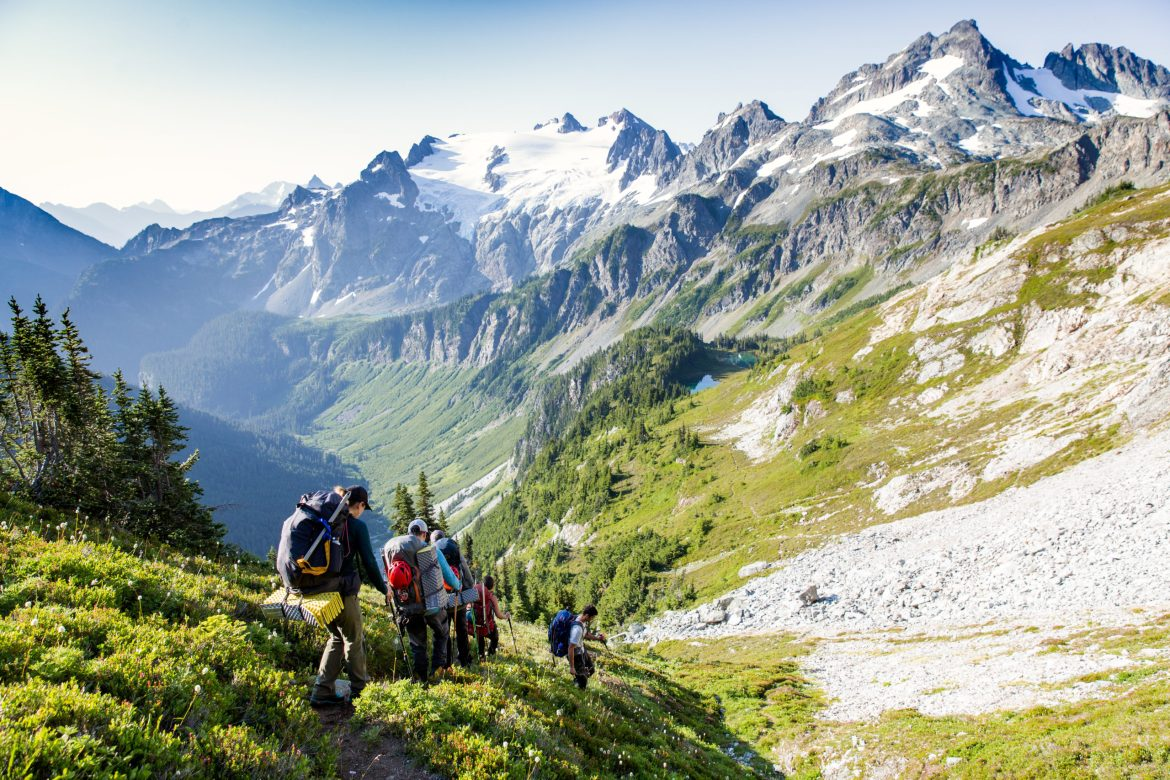 A group of backpackers walk single file along a trail with mountains ahead.
