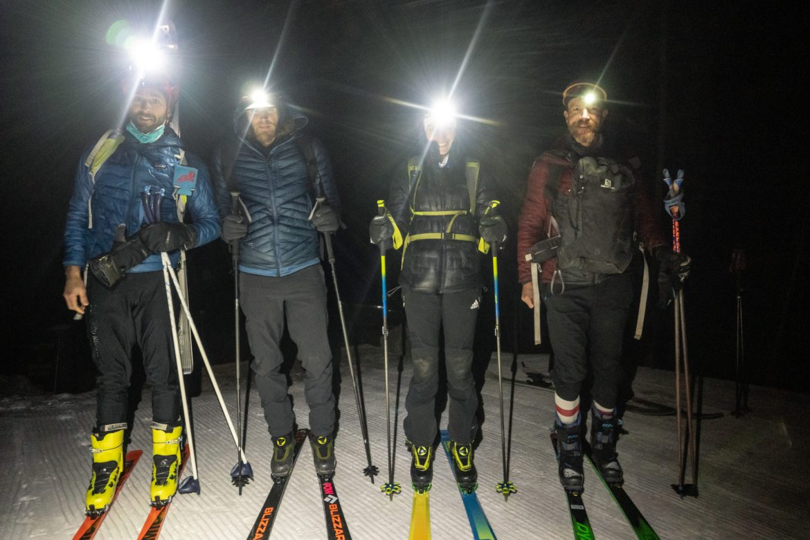 Four skiers stand in the darkness in a line with their headlamps on. They are smiling for the camera.