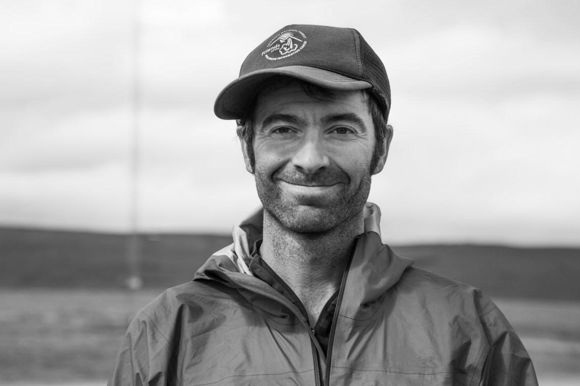Profile image of Luc Mehl. He's smiling at the camera, wearing a trucker hat and a raincoat.