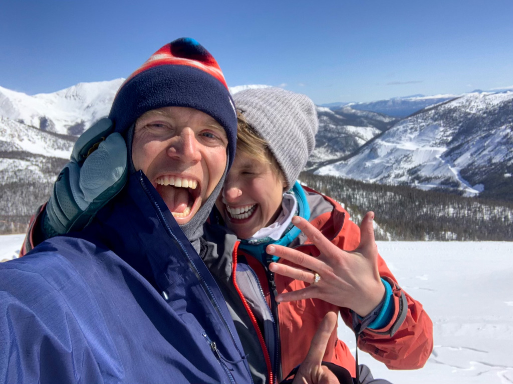 Ian and Phoebe smile in their winter garb on top of a mountain. Phoebe holds her hand out with a ring on it.