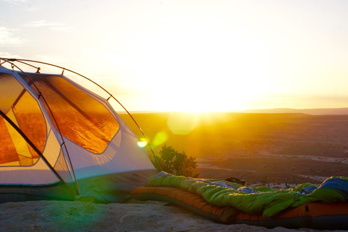 A tent with a sleeping bag and mat next to it in the desert.