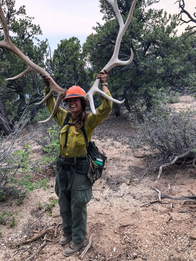 Amanda holds a giant set of antlers next to her head. She's in a hardhat and her firefighting clothes.