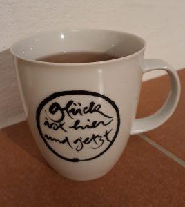 """Teetasse mit der Aufschrift """"Glück ist hier und jetzt"""""""