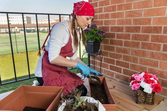 Chica rellenando maceta con compost