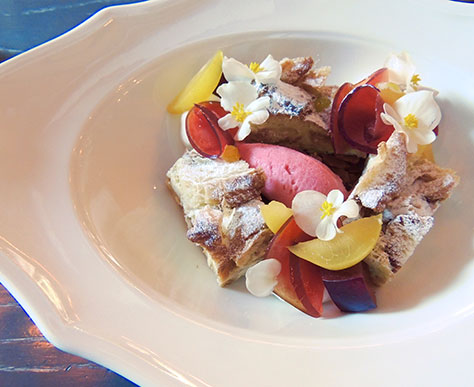 Bread pudding with plum-lemon verbena sorbet and its garnished with garden flowers